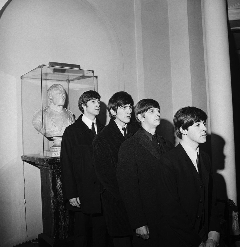 The Beatles beside a bust of Napoleon, 1964.