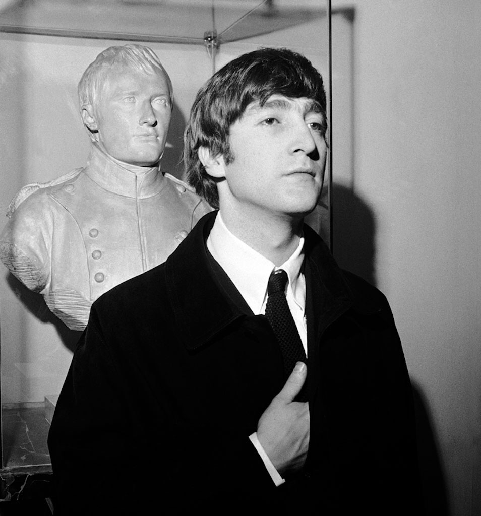 John Lennon beside a bust of Napoleon, 1964.