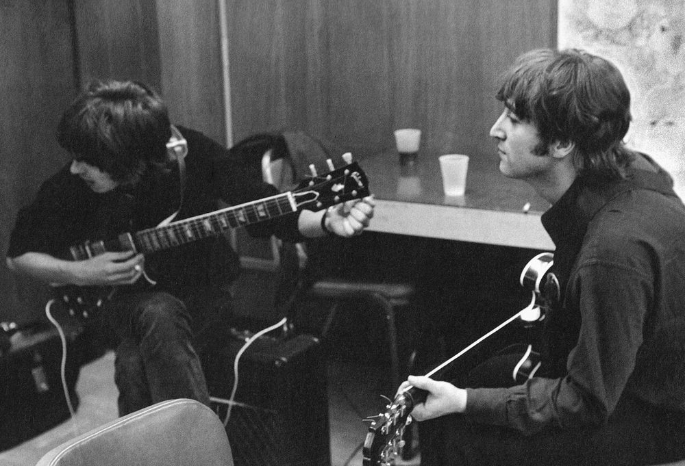 George Harrison and John Lennon tuning up backstage, 1966.