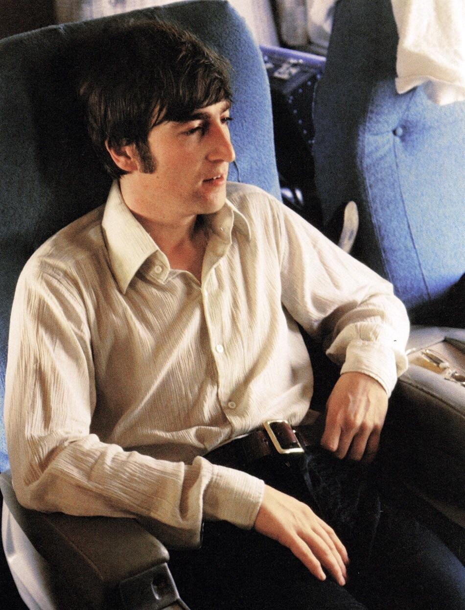 John Lennon relaxing on an airplane, 1966.