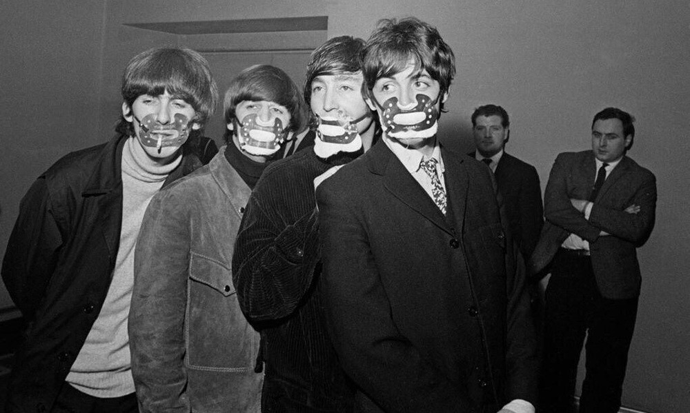 The Beatles wearing smog masks before a gig in Manchester, 1965.