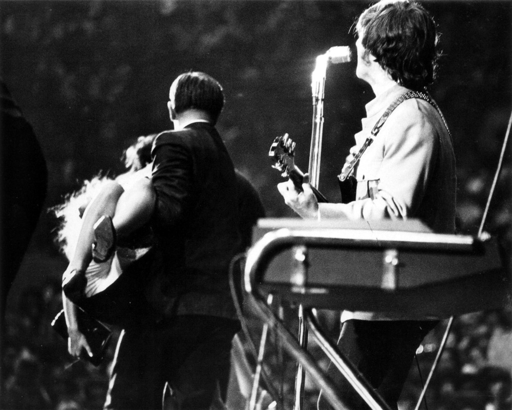 John Lennon watches as a fan gets carried off stage  at the Cow Palace, San Francisco, August 31st, 1965.