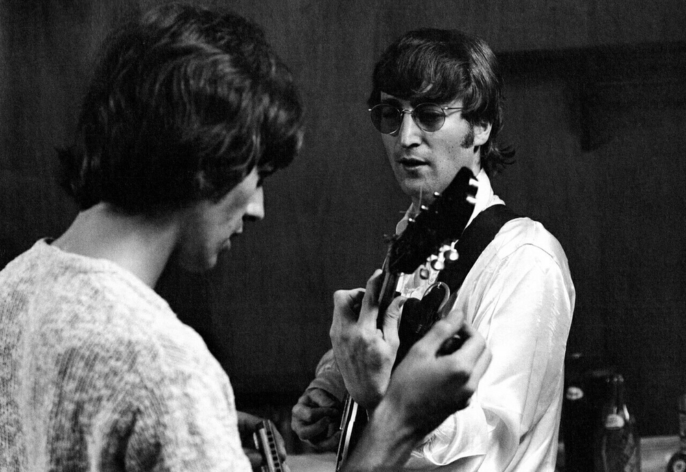 John Lennon and George Harrison tuning up backstage at a gig in the US, 1966.