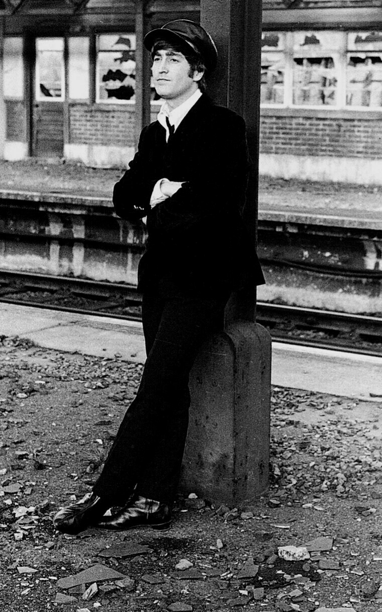John Lennon at a Beatles' photo shoot by a train station, 1964.
