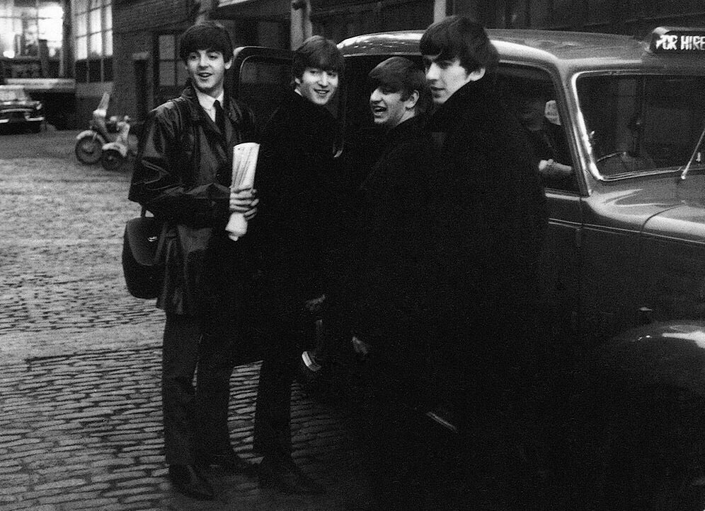 The Beatles getting in a taxi, 1964.