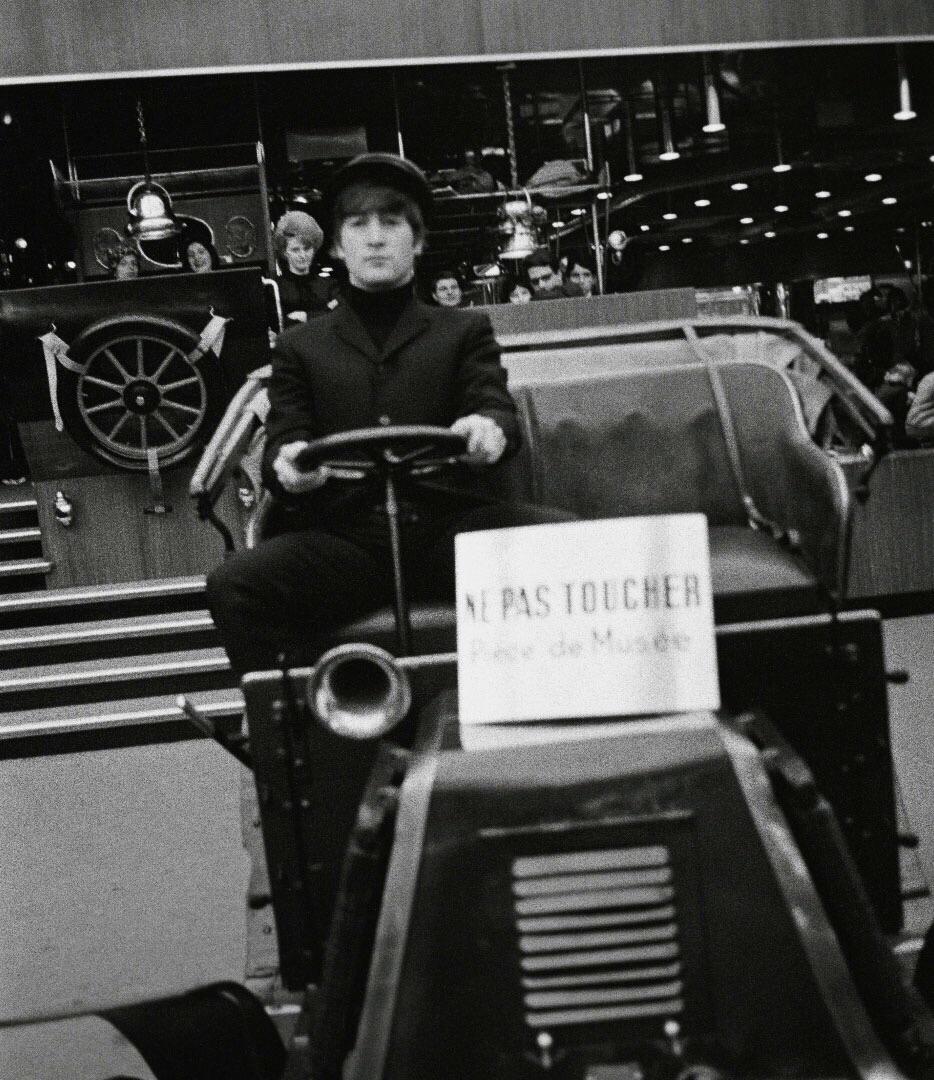 John Lennon driving a vintage car, 1964.