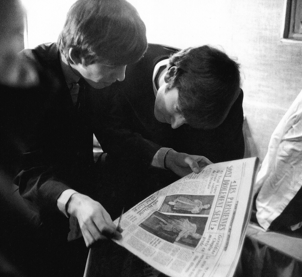 George Harrison and John Lennon reading a newspaper, 1964.