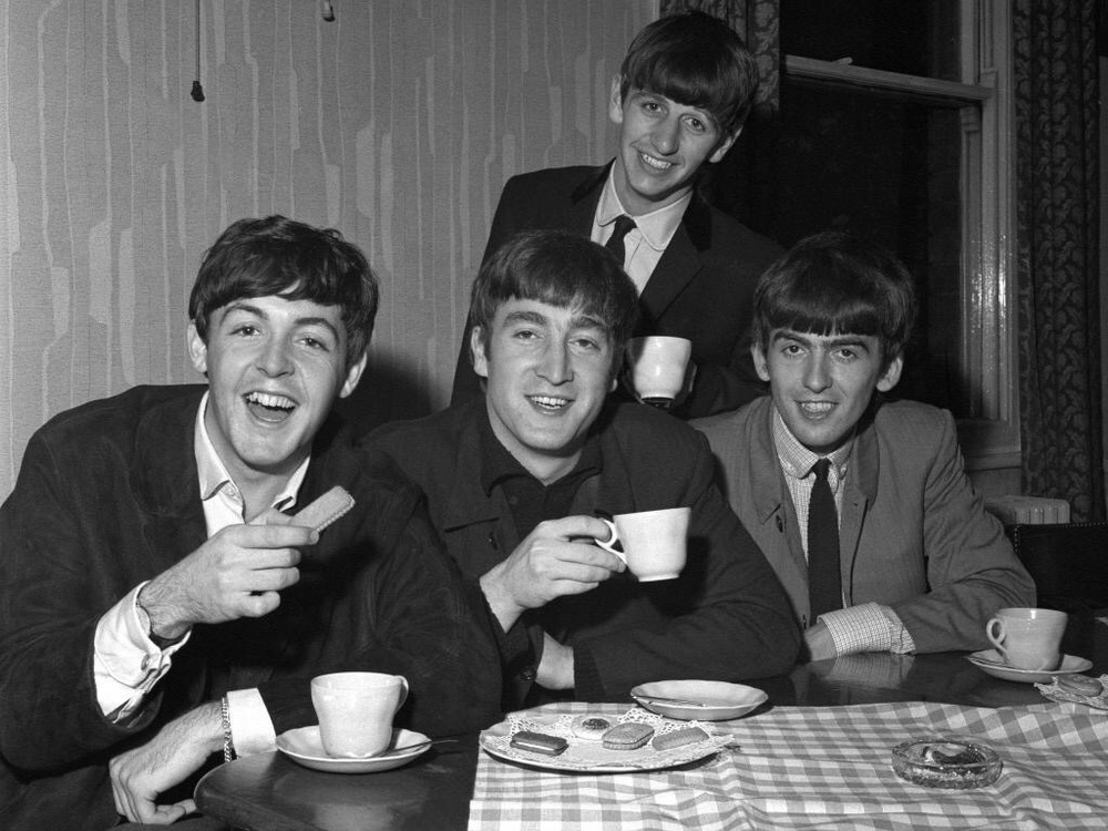 The Beatles enjoying tea and biscuits, 1963.