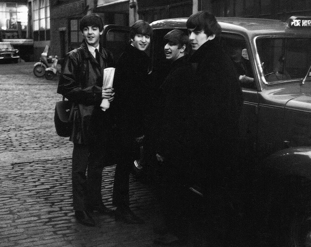 The Beatles catching a cab, 1964.