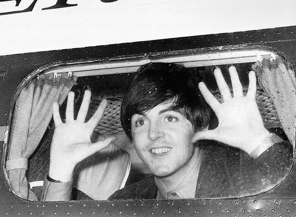 Paul McCartney on a plane, 1964.