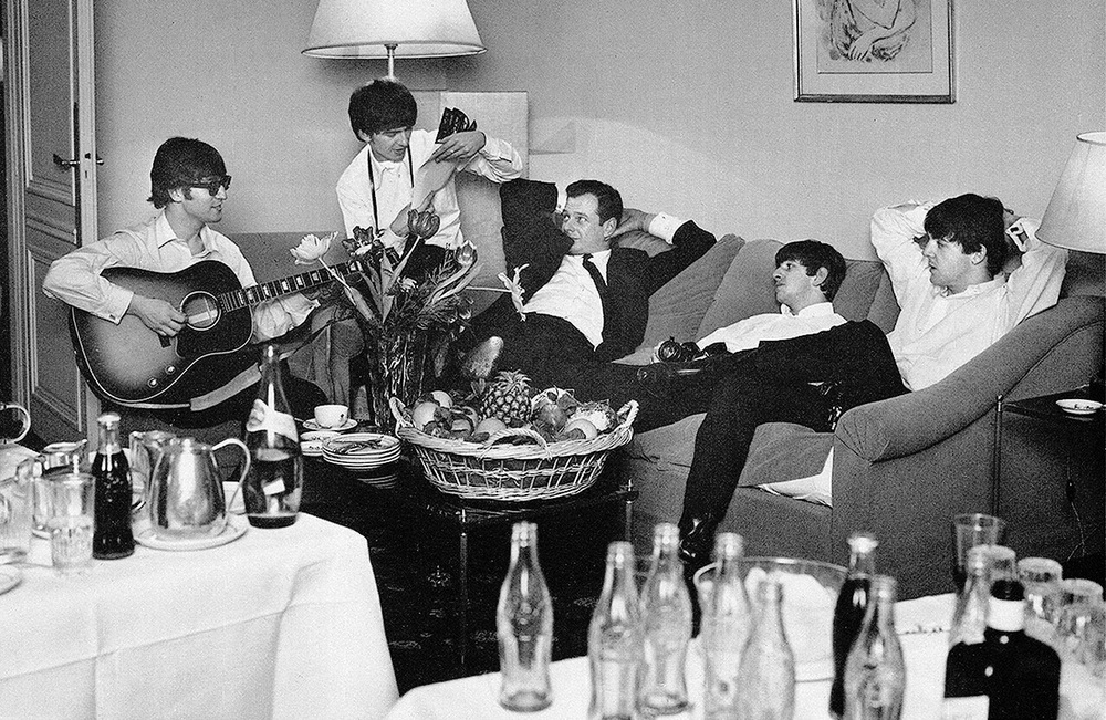 The Beatles in a hotel room with Brian Epstein, 1964.