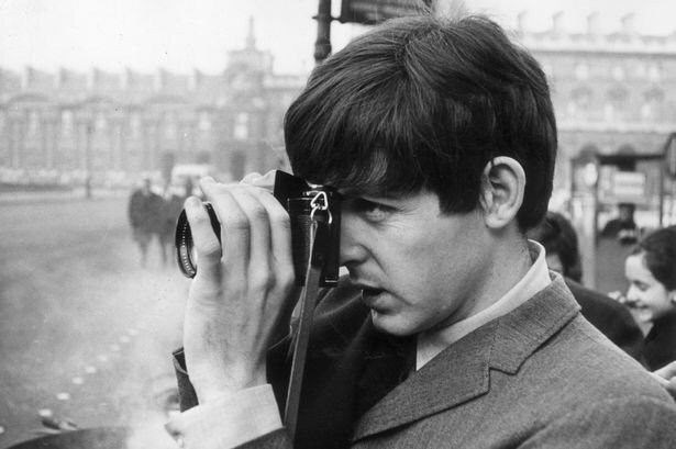 Paul McCartney photographed taking a photograph, 1964.