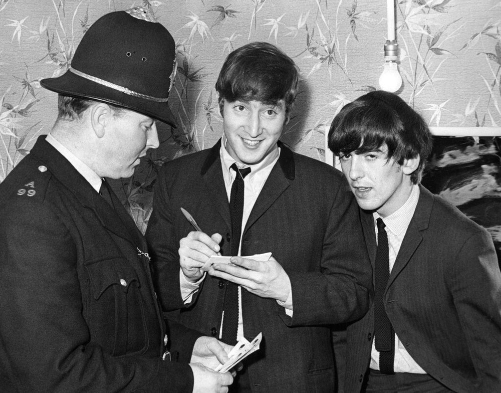John Lennon and George Harrison signing an autograph for an English policeman, 1963.