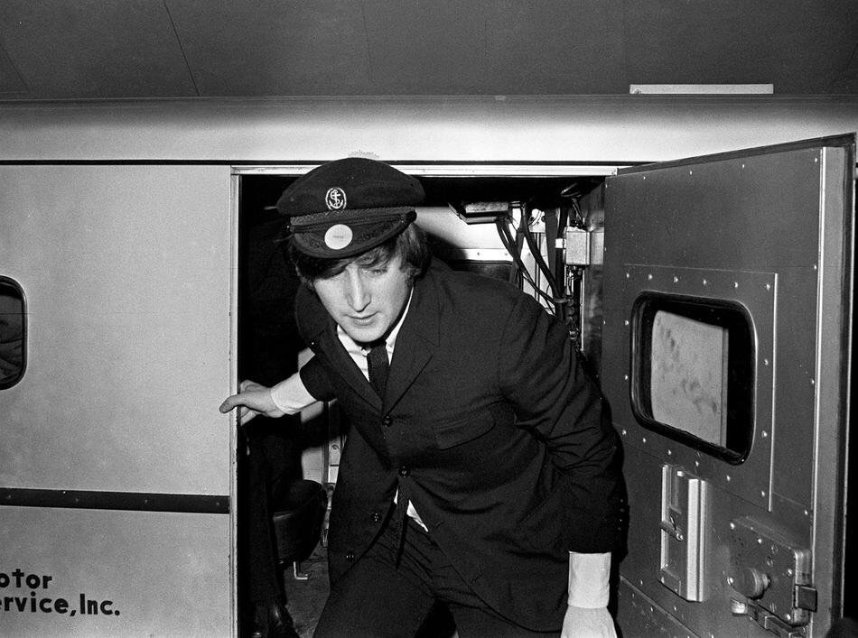 John Lennon exiting an armoured car while on tour with the Beatles.