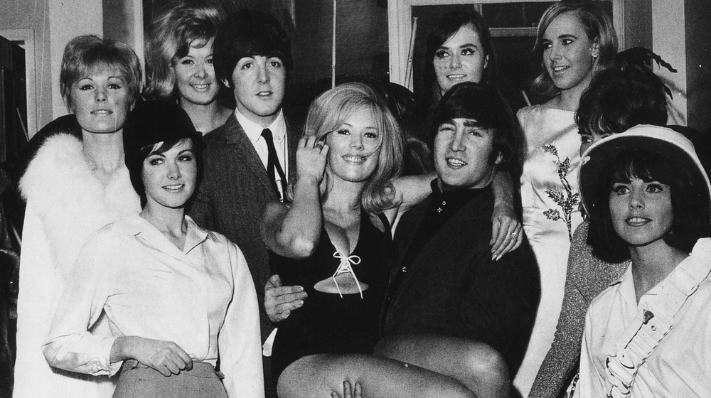 John Lennon and Paul McCartney with a group of showgirls, 1964.