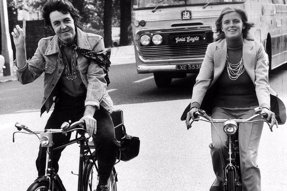 Paul and Linda McCartney riding bikes, circa 1972.