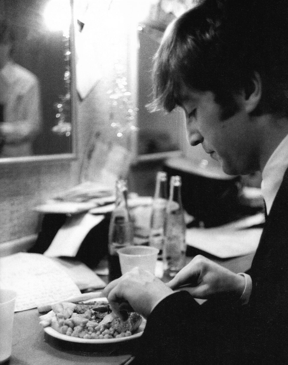 John Lennon eating sausages, chips and beans, 1964.