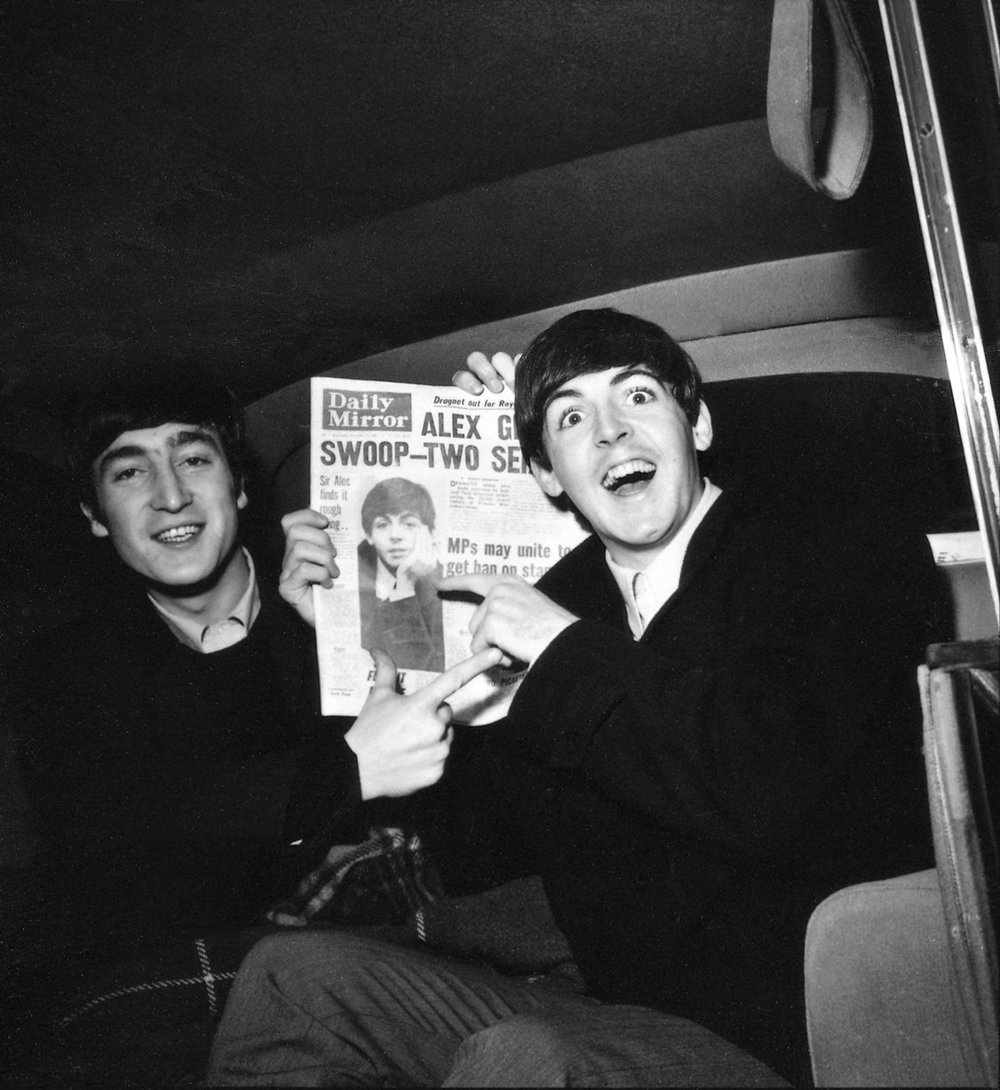 Paul makes the front page, John Lennon & Paul McCartney with copy of Daily Mirror Newspaper in Plymouth during their Autumn Tour. The group had to cancel the previous evening's show at the Guildhall in Portsmouth due to Paul's ill health when he collapsed in the dressing room. 13th November 1963.
