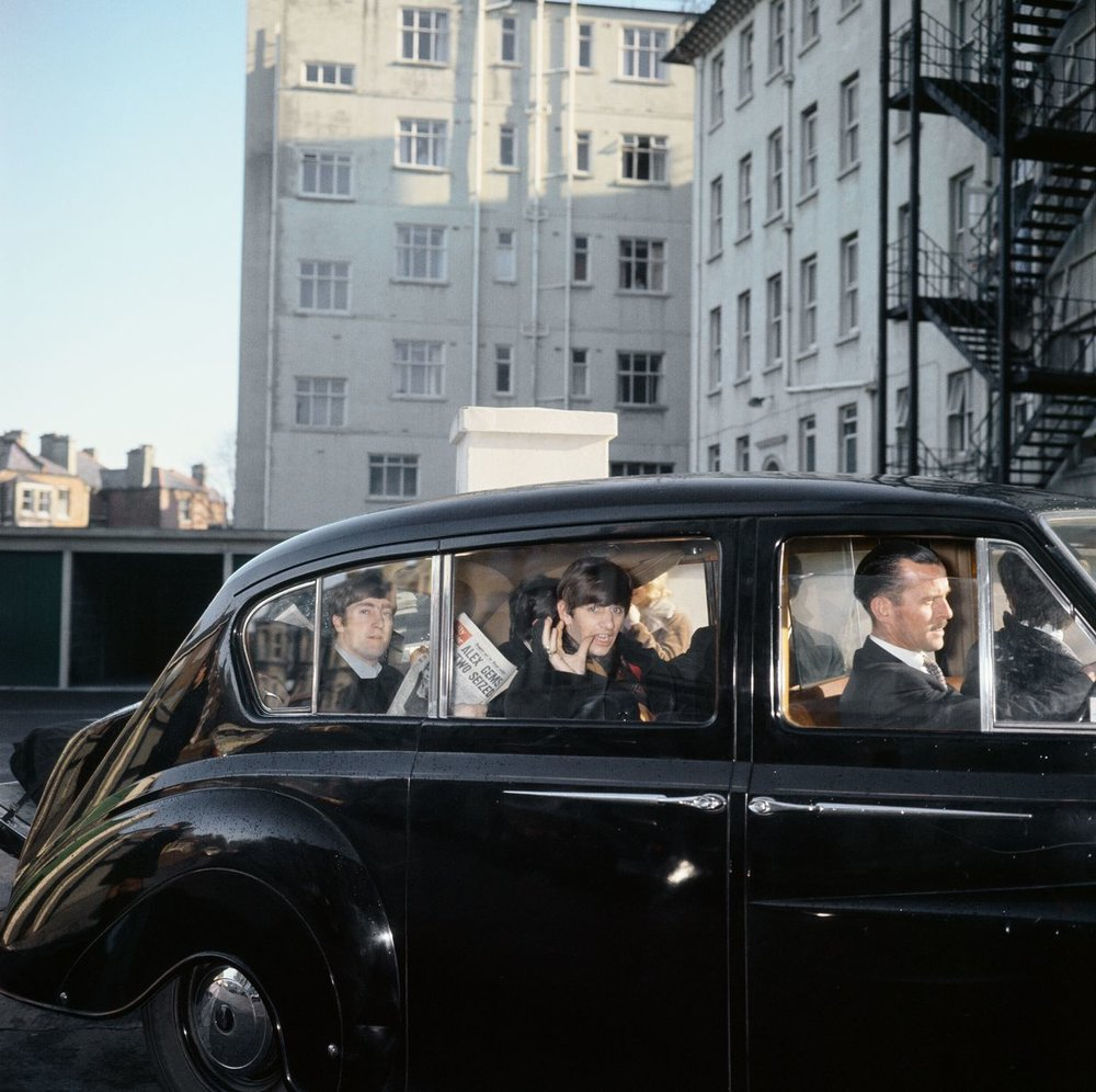 The Beatles John Lennon and Ringo Starr can be seen in the back of a black limosine being driven along the road in Plymouth. John is holding a copy of the Daily Mirror 13th November 1963.
