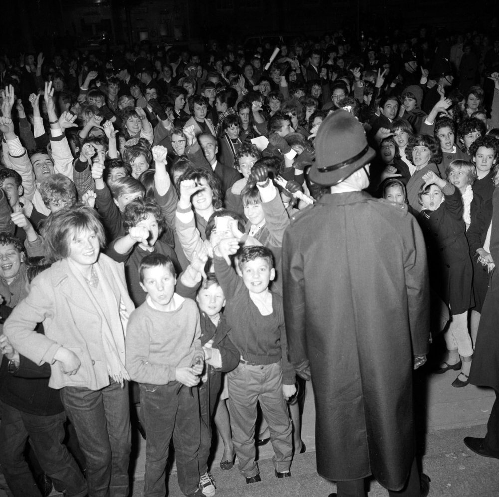 The Beatles November 1963 A policeman stands guard as fans of The Beatles cheer and scream as the band play a gig in Plymouth