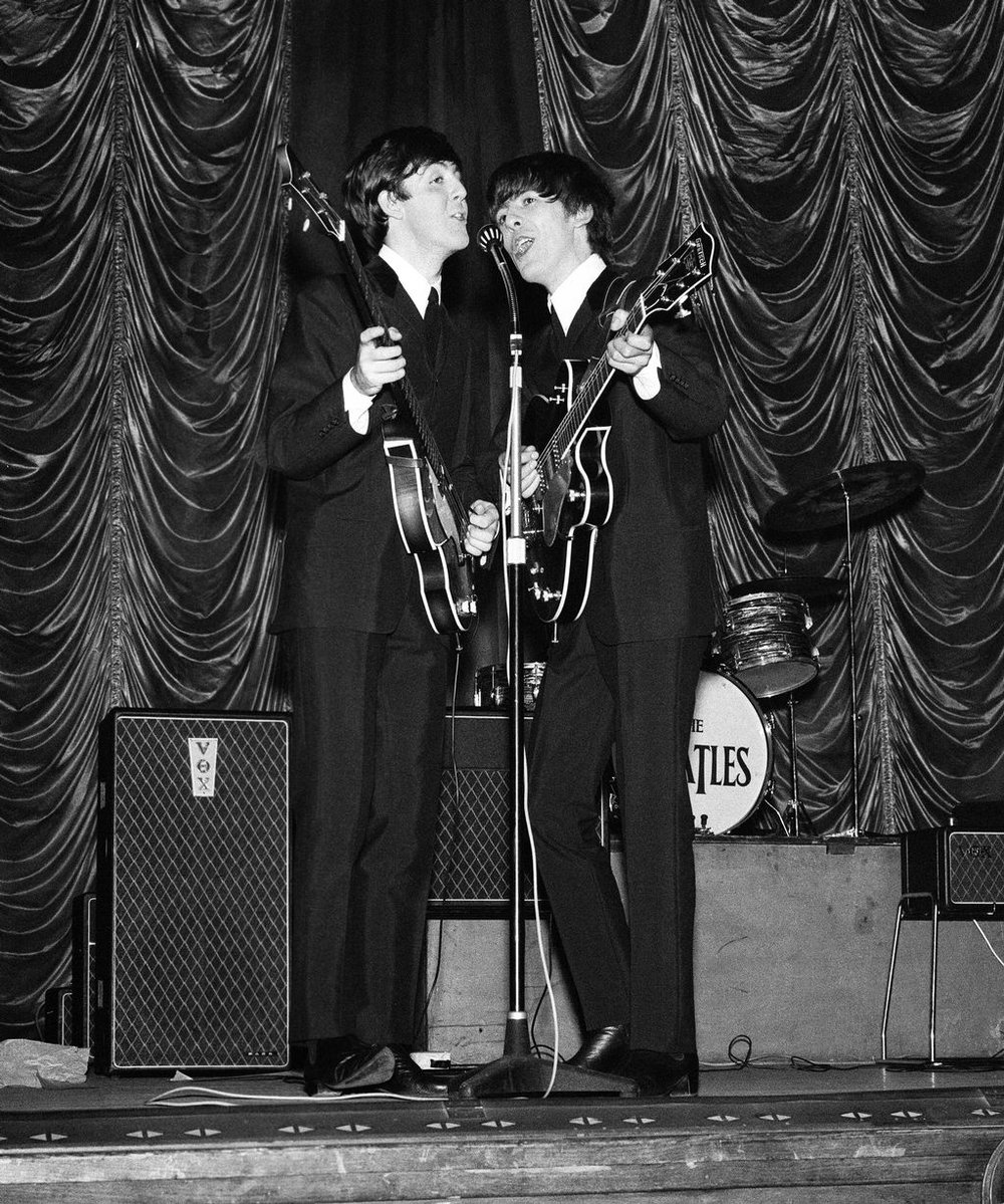 Plymouth 13th November 1963. Paul McCartney and George Harrison share the microphone during their gig.