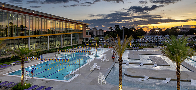 [Photo Description: View overlooking the LSU UREC outdoor pool at sundown where Anchor Splash will take place.]