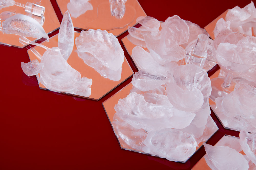 "Amarus Ends  – detail Resin and acrylic mirror; 30x16x4.75"" [breaks apart into an edition of ten]. Photographed by Tamara Legér.  Strewn haphazardly across a mirrored plane lays the remnants of an extravagant meal left to fester. An assortment of emptied oysters sit piled, their little spills and dribbles marking the surface below. The entrée's exhausted accoutrements dot the scene. Lemon wedges, pinched rinds and tiny utensils are scattered about; a drunk cocktail stands as tall as the mound, another, broken and spilling its dregs into the array; cigarettes, butted out post-meal into the husks. A small pile of maraschino stems from a Manhattan overstuffed, provides a clue towards the title of the work. Each object makes its materiality known–clear resin derived from the pressure of millennia–oysters cast in wretched permanence see their reflection below in refracted light."