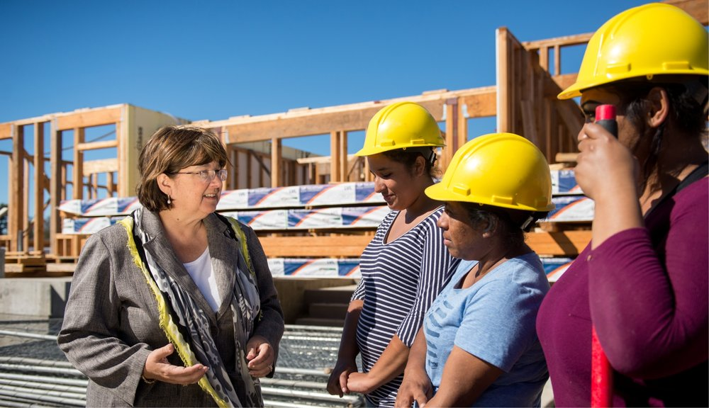 Julie speaks with a group of Women working to build their own homes through our city sponsored self-help homeownership program at Catalina Homes