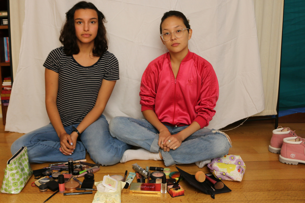 Tatiana (left) and Sara (right) with the piles of makeup from their daily routines.