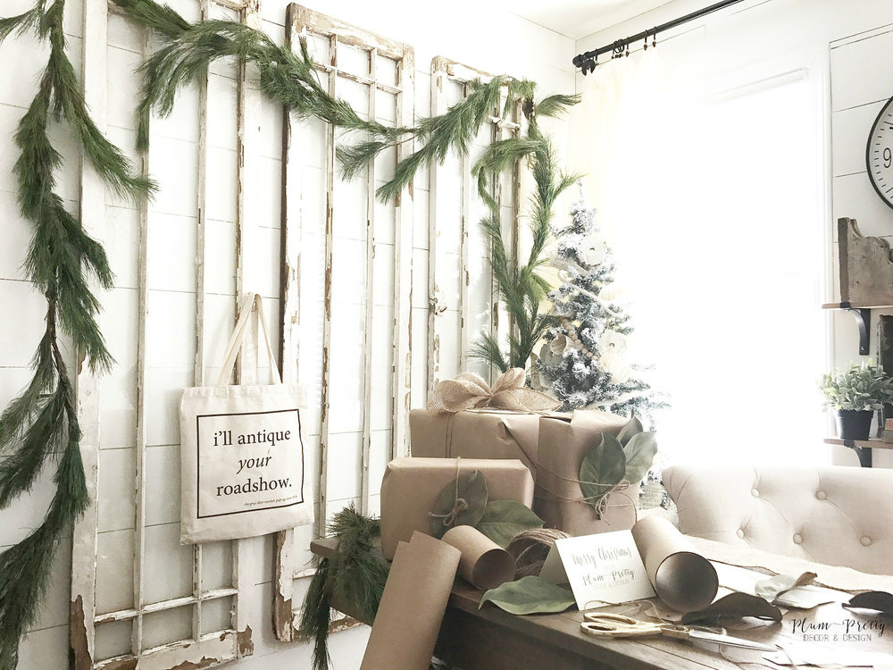 Farmhouse Office Decorated for Christmas. Antique windows with fresh garland and neutral wrapping station- Plum Pretty Decor and Design
