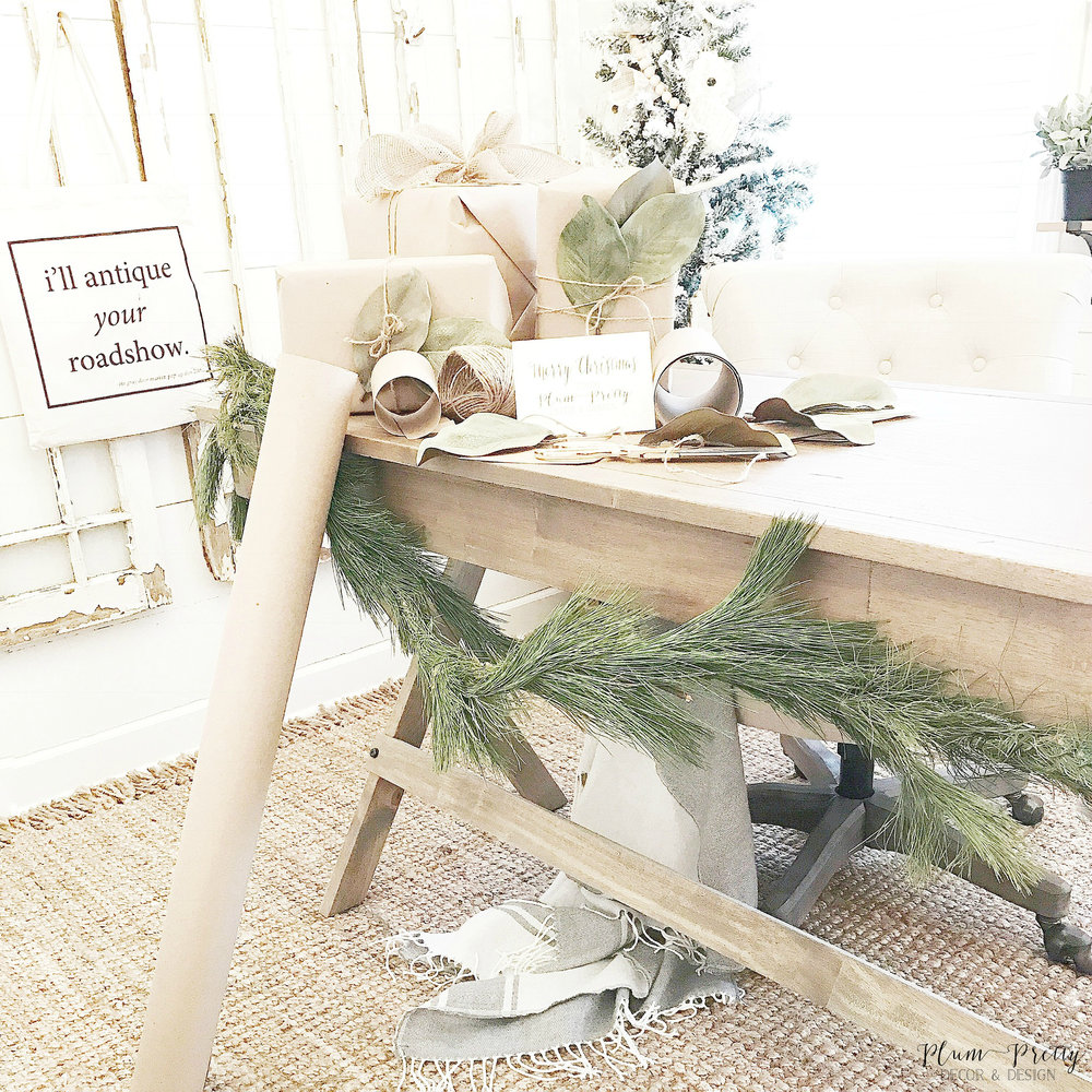 Christmas Farmhouse Style Office. Decorated with a jute rug, simple wood desk, tufted linen chair, antique windows, and fresh greenery- Plum Pretty Decor and Design