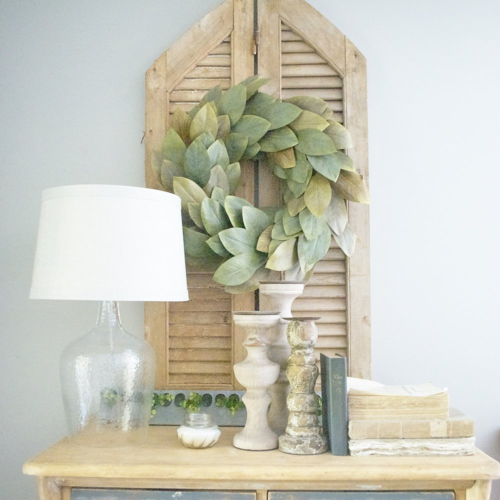 Neutral Decor Advice- Try Using Old Books and Metal (Like how I layered in a metal chicken feeder with greenery) in Your Decor- By Plum Pretty Decor and Design