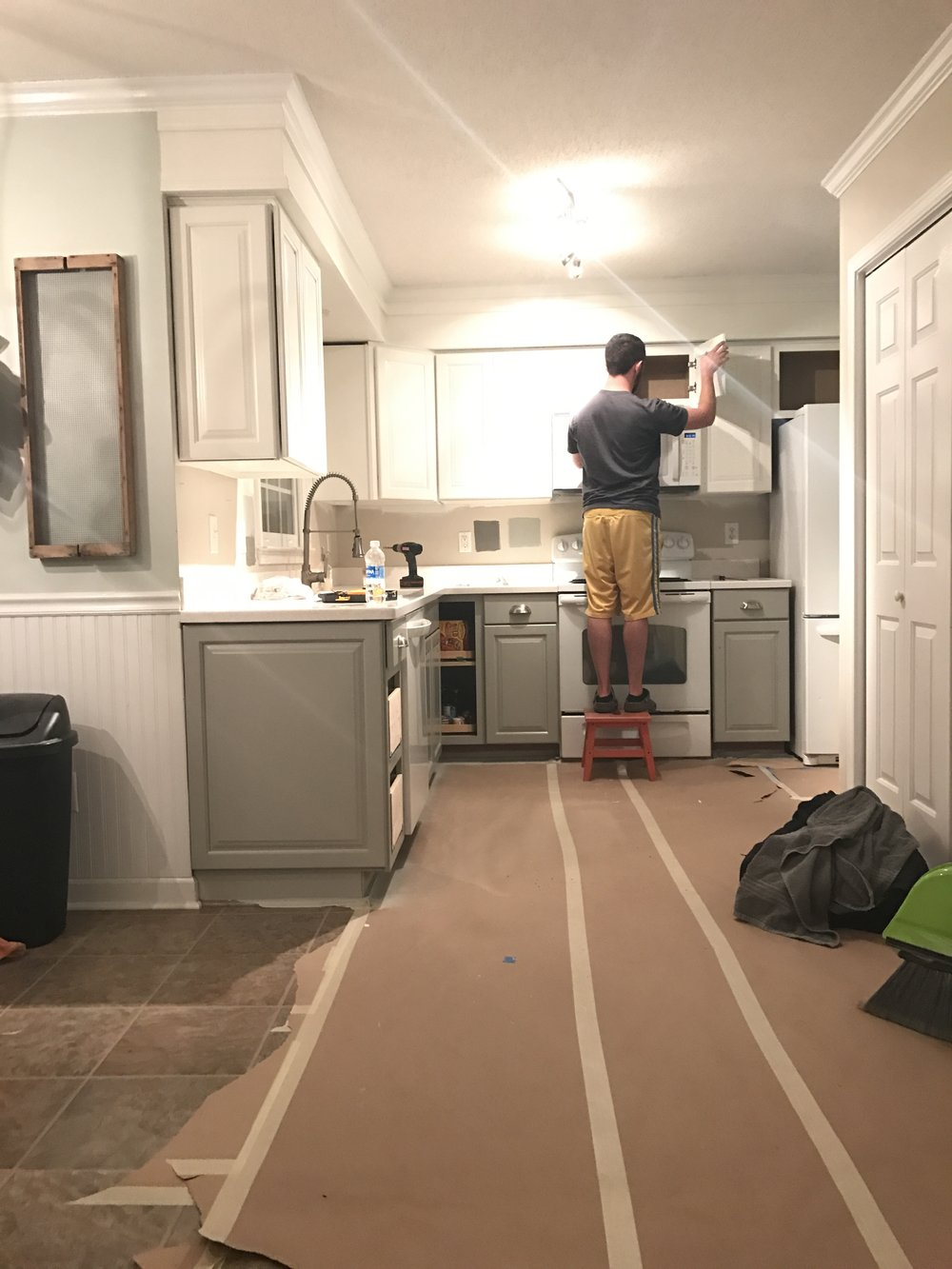 Painted_Kitchen_Cabinets_Putting_Doors_Back_On.JPG