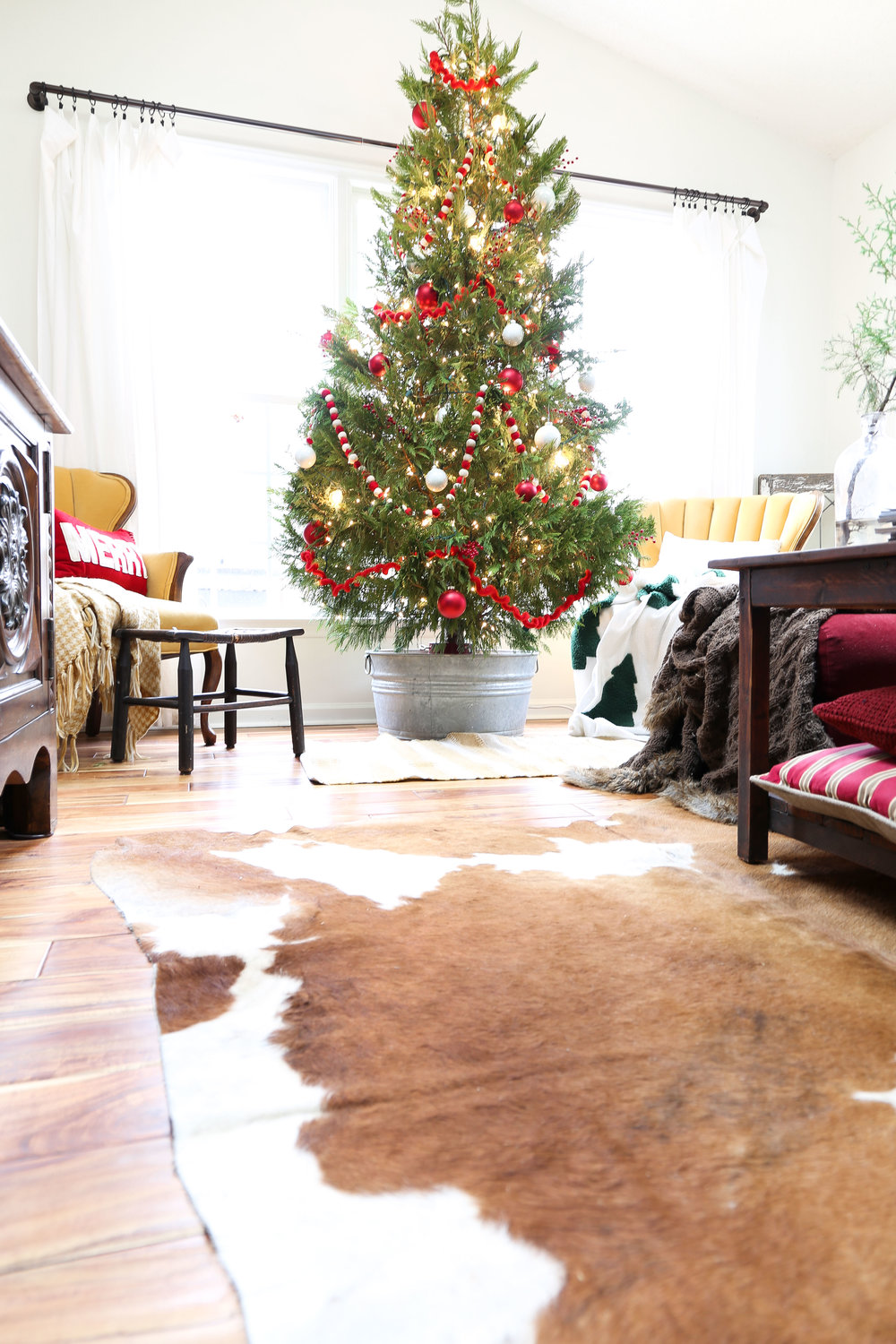 Christmas Family Room with Cow Skin Rug and Simple Christmas Tree- By Plum Pretty Decor and Design