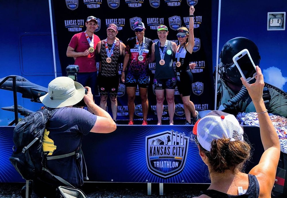 Coach Amy on the podium (far right) while her coach takes a photo with her phone.