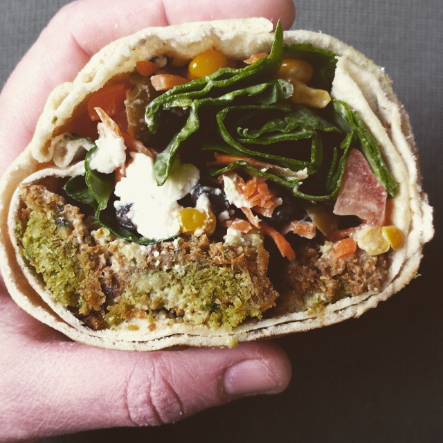 Falafel Pita with spinach, tomato, carrot, corn, black beans, feta, and tahini