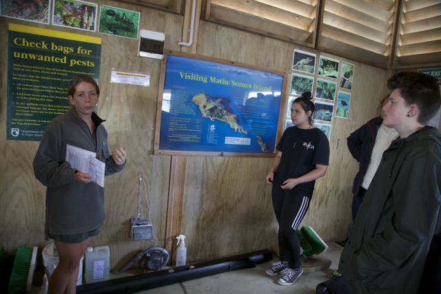 Students checking their belongings to ensure they are free of invasive species and materials like mice and seeds while visiting Matiu Somes Island.
