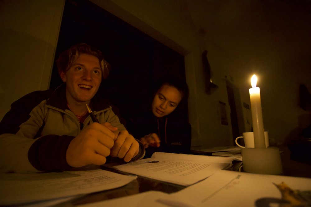 Students from Aotea College study by candle light in Turere Hut in the Rimutakas.