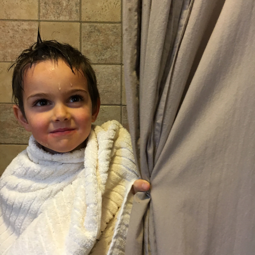 Asher rocking the Natural Stripe towel behind the Mushroom Voile shower curtain