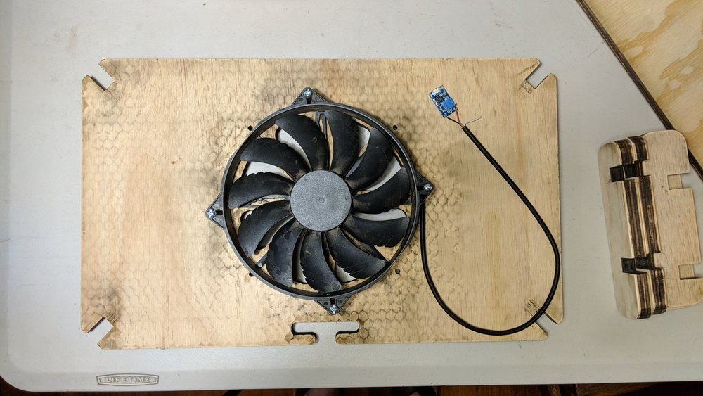 The cooling fan is mounted to the underside of the laptop shelf
