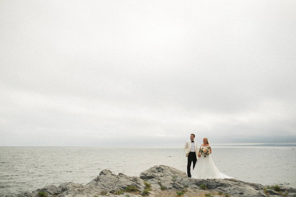 Top of 17 | Number 8 |Emily & Anthony | Cliffs of Newport  Fuji XT2 | Fuji 10-24 f4  After I had finished shooting some incredible portraits with Emily, Anthony and their wedding party I stepped back to let their filmmakers roll some footage of them on the cliffs. When they both looked right and Anthony put his hand in his pocket I clicked on my 10-24 and fired a couple frames. The grain and the rain... that's what makes this photo so lovely. This is easily my favorite wedding portrait I have ever photographed. If I one day retire from this crazy job, and do some kind of career top 10, you can be certain this photo will be there.