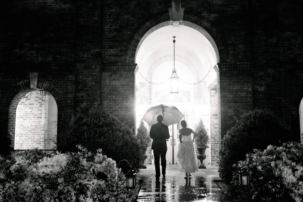 Top of 17 | Number 5  | Jessica & Colin |  The New Haven Lawn Club (in the rain!)  Fuji XT2 | Fuji 23 f2  It rained on Jessica and Colin's wedding day... hard. It really didn't stop. Nor did it stop them from having one of the more memorable weddings of my season. Rain is what you make it. It poured on mine and Corey's wedding day, but we had a blast. In this photo, after we had finished some rainy evening portraits, I stayed back as the couple made their way inside. The photos we took were cool, but this quick and candid moment is the clear winner. I love the mood, the drama, the soaking wet pathway, the unlit candles, the way she's hiking her dress...it's everything a photo in the rain should be. If Jessica and Colin werent so willing to come stand in a downpour with me, it never would have happened. I'm so glad they did.