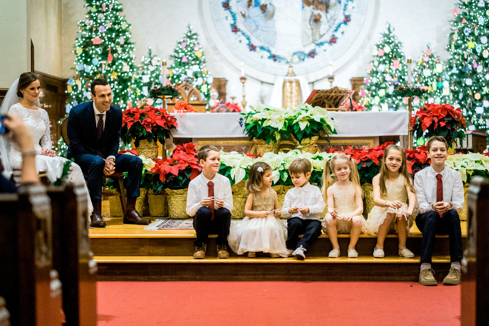 Honorable Mention 3 | Kayla & Matt | St. Mary's - Longmeadow, MA  Sony a9 | 28 f2.0  Just a couple of weeks ago on December 28th, Kayla and Matt were married by a long time family friend, and reverend in their church. During the service he invited all of the kids in the room to come sit and be a part of the ceremony. I've shot a lot of weddings, and have never seen something like this in a church before. As a father of two, this was an awesome and memorable moment.