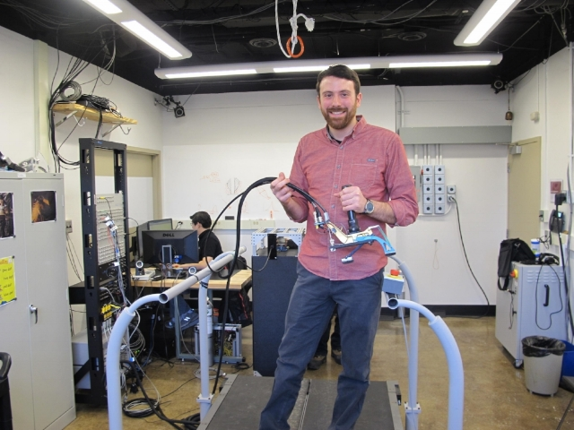 Josh Caputo (HuMoTech founder and CEO) holding the prosthetic foot emulator in the CMU Experimental Biomechatronics Lab. Photo credit: Mark Nootbaar / 90.5 WESA.