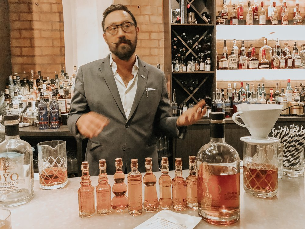Society Lounge owner Joey Fredrickson talks about infused whiskeys and bourbons. Pictured is a chamomile-whiskey infusion.