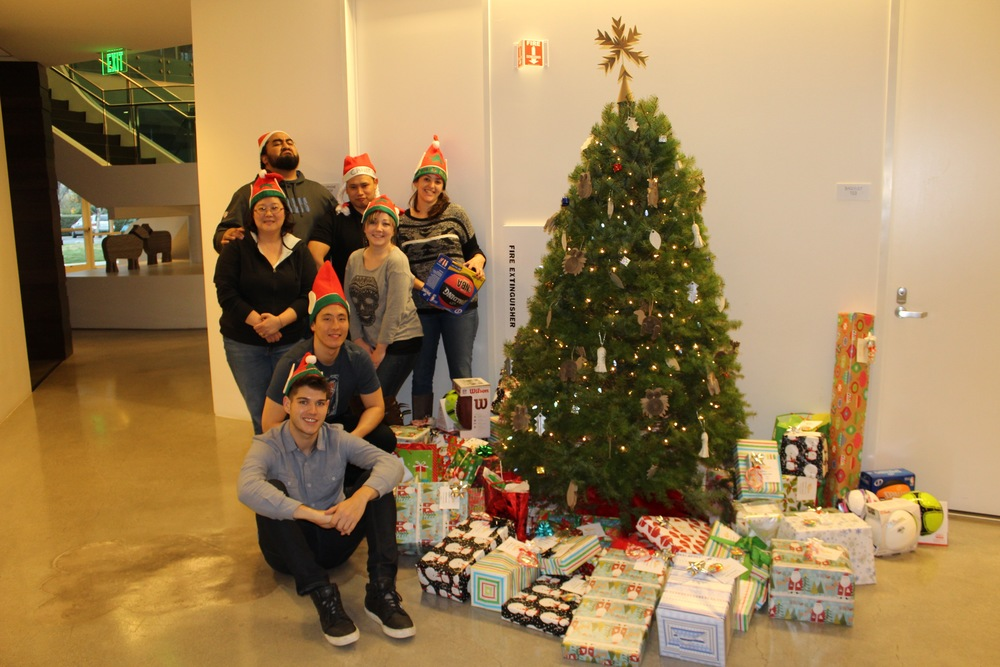 PaperSeed California members & volunteers strike a pose next to the Giving Tree before leaving to drop off gifts.      Top Row:  Sioeli Palu, Garen Suen, Megan Lima  Middle:  Wendy Ju, Diana Gray      Front:  Chris Cho, Max Nelson