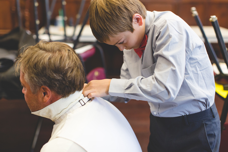 orange county regional history center intimate wedding groom and son getting ready fastening bowtie