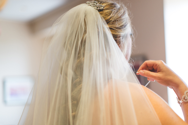 orange county regional history center intimate wedding bridal veil bride putting on necklace before wedding