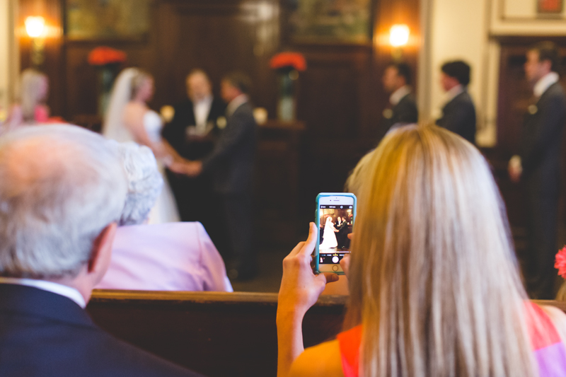 orange county regional history center intimate wedding guest taking a cell phone photo during ceremony