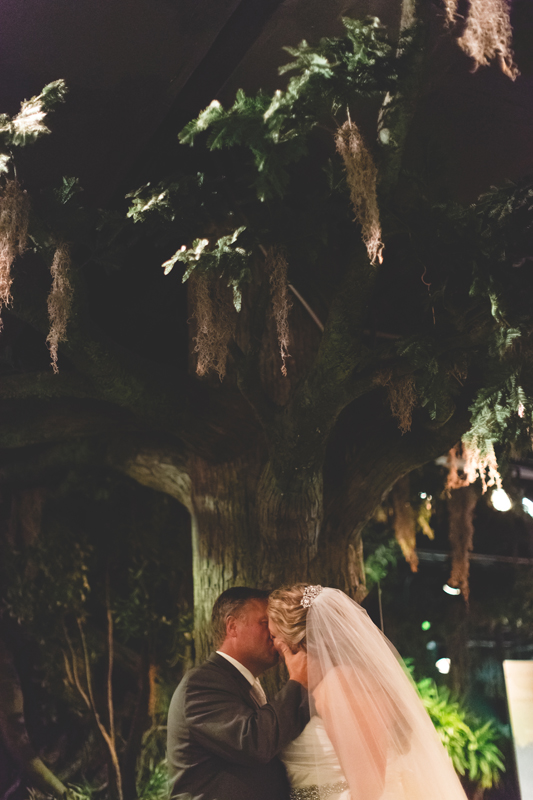 orange county regional history center intimate wedding bride and groom kissing under huge indoor tree inside of museum